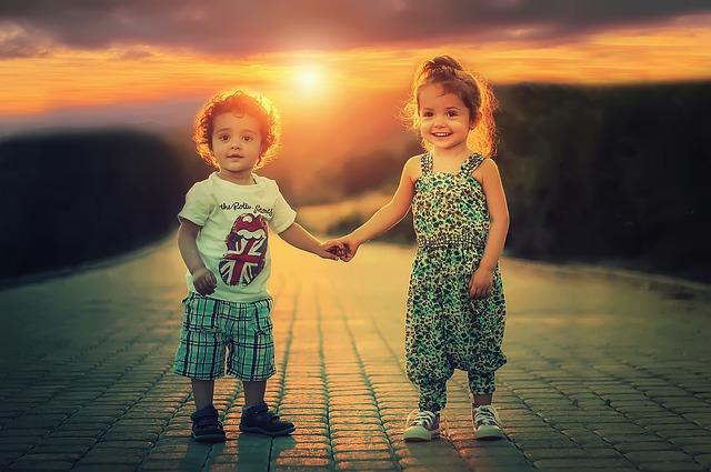 deux enfants qui se tiennent la main au soleil couchant