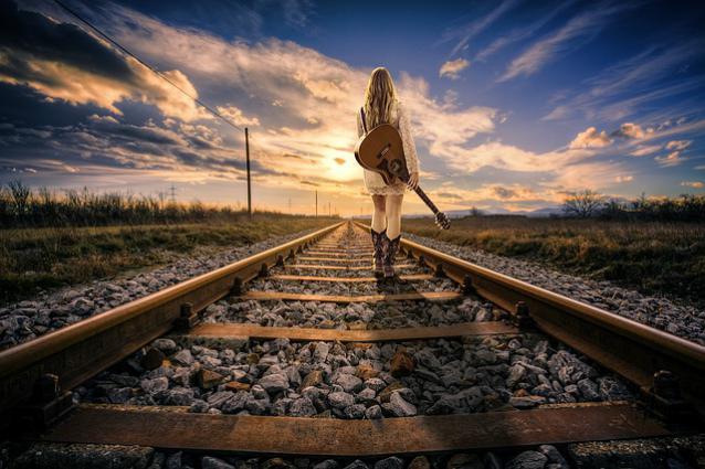une femme marchant sur les rails, guitare à la main