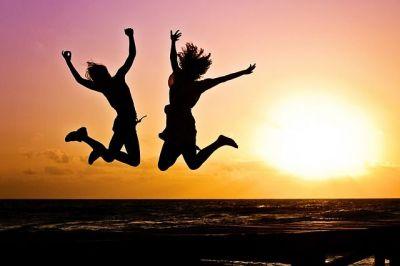 deux femmes heureuses font un grand saut à la plage